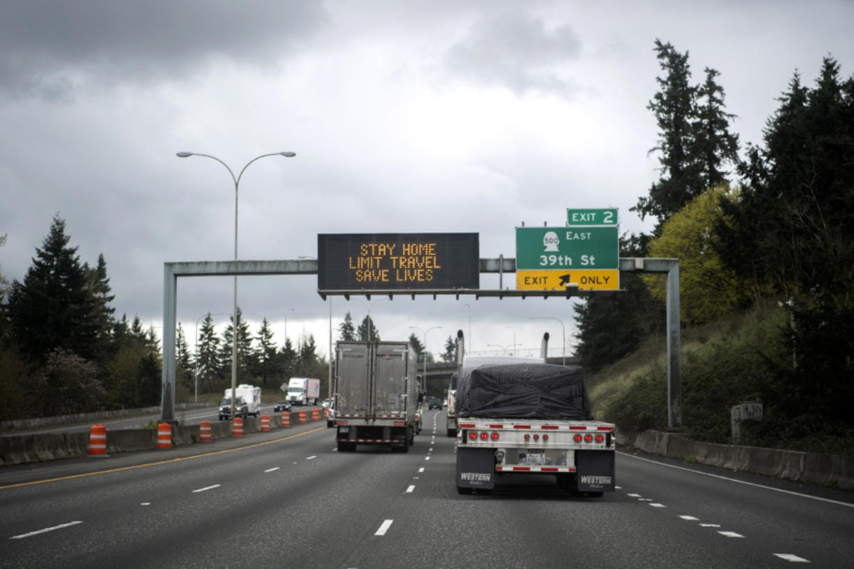 "Trucks drive under a sign on Interstate 5 reading ""Stay home, limit travel"" in Vancouver on Tuesday. Transportation is one segment not impacted as deeply, although airlines are hurting."