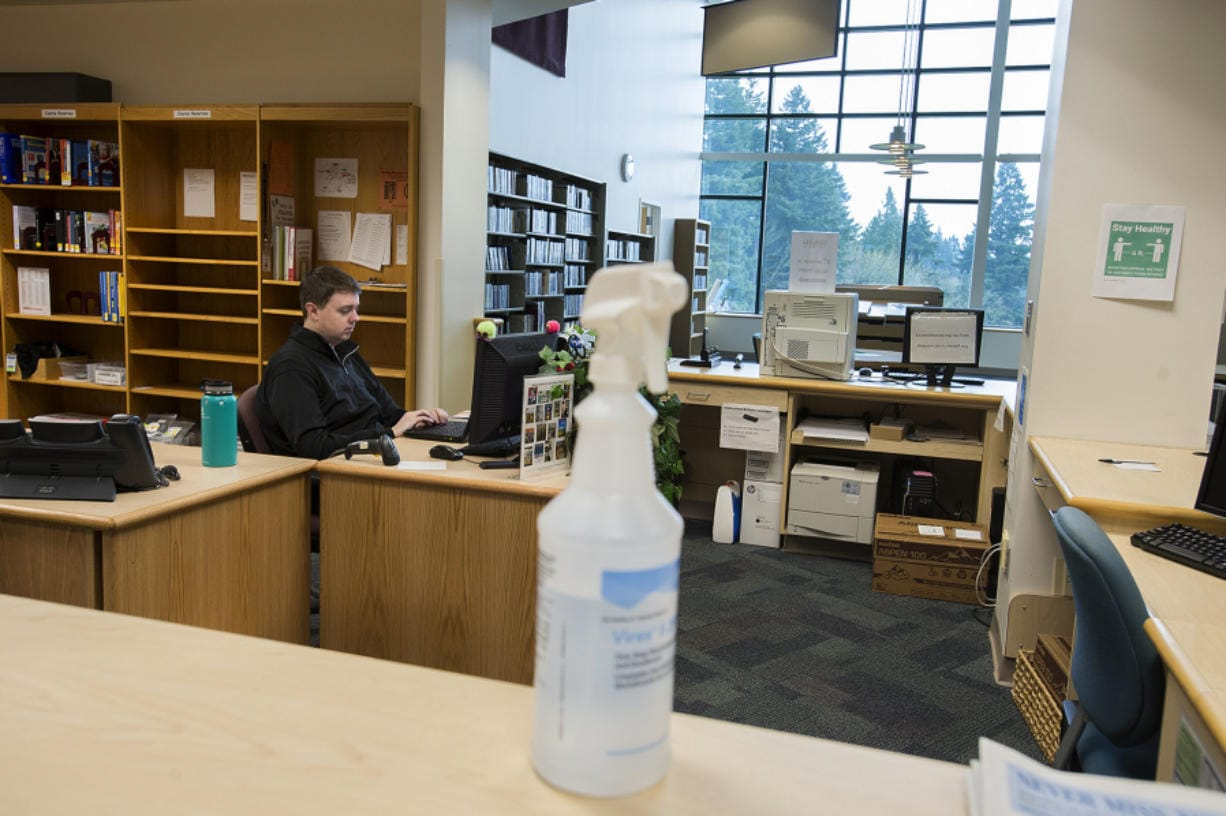 """A bottle of disinfectant is seen on the front desk of the library at Washington State University Vancouver as junior Travis Lynn works nearby amid concerns of COVID-19 on Wednesday morning. Campus closed Wednesday afternoon following Gov. Jay Inslee's """"Stay Home, Stay Healthy"""" order to stop the spread of COVID-19. (Photos by Amanda Cowan/The Columbian)"""