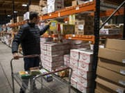 Tim Boris of Ridgefield picks out items at SteBo's Food Service in Vancouver on Friday. Normally SteBo's only sells in bulk to restaurants and stores, but the company is temporarily selling to individual buyers, too.