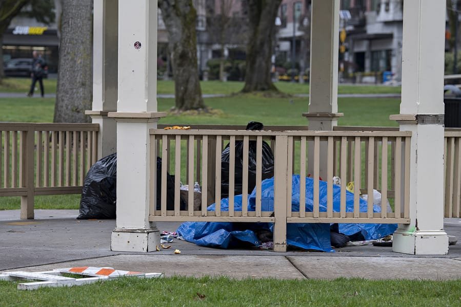 A person experiencing homelessness takes shelter underneath a gazebo at Esther Short Park on Wednesday morning.