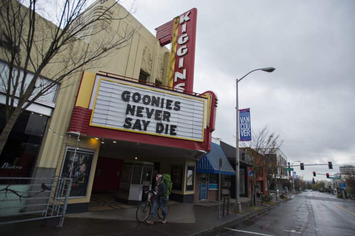 Vancouver resident Elizabeth Hay walks her bike past Kiggins Theatre on a nearly empty Main Street on Friday morning. Kiggins is currently closed but has partnered with an independent film streaming service.