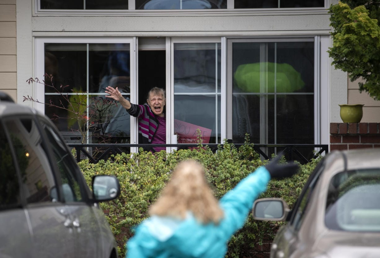 Touchmark resident Gladys Meier waves at staff members as an outdoor parade moves by her window through the parking lot at the senior living community in Vancouver on Thursday.