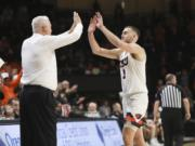 Oregon State's Tres Tinkle (3) high-fives his father, Oregon State head coach Wayne Tinkle, as Tres is subbed out in the last minute of his final home NCAA college basketball game, against California, in Corvallis, Ore., Saturday, March 7, 2020.
