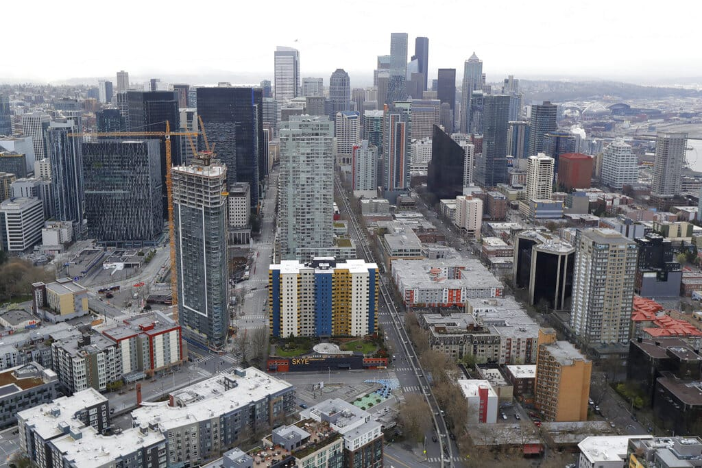Empty streets are seen in downtown Seattle as viewed from from the roof of the Space Needle, Thursday, March 26, 2020, in Seattle. Most people in the usually bustling city were off the streets Thursday as Seattle began a state-wide stay-at-home mandate amidst one of the worst outbreaks of the new coronavirus in the U.S. (AP Photo/Ted S. Warren)