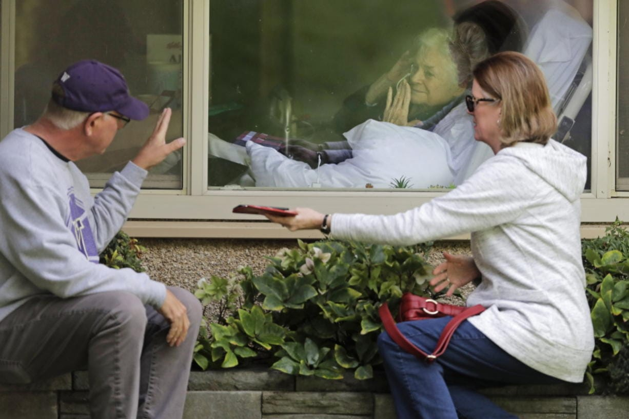 Judie Shape, center, who has tested positive for the coronavirus, blows a kiss to her son-in-law, Michael Spencer, left, as Shape's daughter, Lori Spencer, right, looks on, Wednesday, March 11, 2020, as they visit on the phone and look at each other through a window at the Life Care Center in Kirkland, Wash., near Seattle. In-person visits are not allowed at the nursing home.  The vast majority of people recover from the new coronavirus. According to the World  Health Organization, most people recover in about two to six weeks, depending on the severity of the illness. (AP Photo/Ted S.