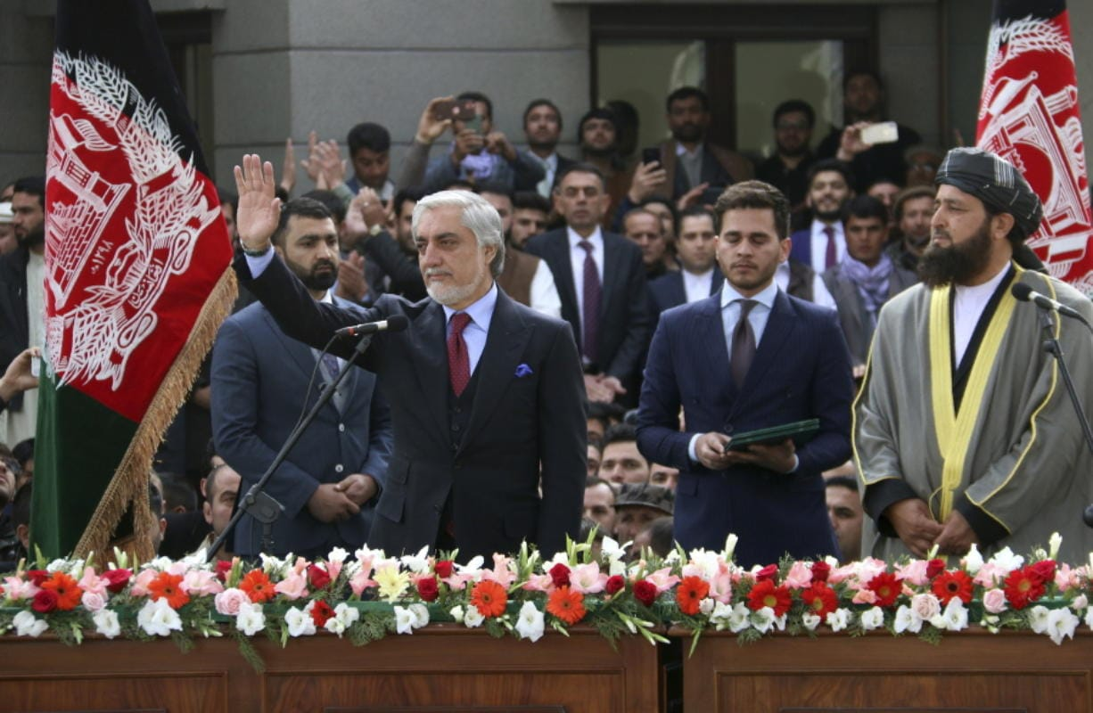 In this Monday, March 9, 2020, photo, Afghanistan's Abdullah Abdullah, front left, greets his supporters after being sworn in as president in Kabul, Afghanistan. Washington moved forward Tuesday on its peace deal with the Taliban, launching its troop withdrawal, while praising Afghanistan's newly installed President Ashraf Ghani's promise to proceed with a Taliban prisoner release as well as cobble together a team to start negotiations with the insurgent group. But the dueling presidential inaugurations a day earlier with Ghani's rival, Abdullah Abdullah also being sworn in as president is indicative of the uphill task facing Washington's peace envoy Zalmay Khalilzad as he tries to get Afghanistan's bickering leadership to come together.
