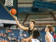 Battle Ground's Kaden Perry lofts the ball off the backboard to himself for a dunk in a 4A State round-of-12 game Wednesday at the Tacoma Dome.