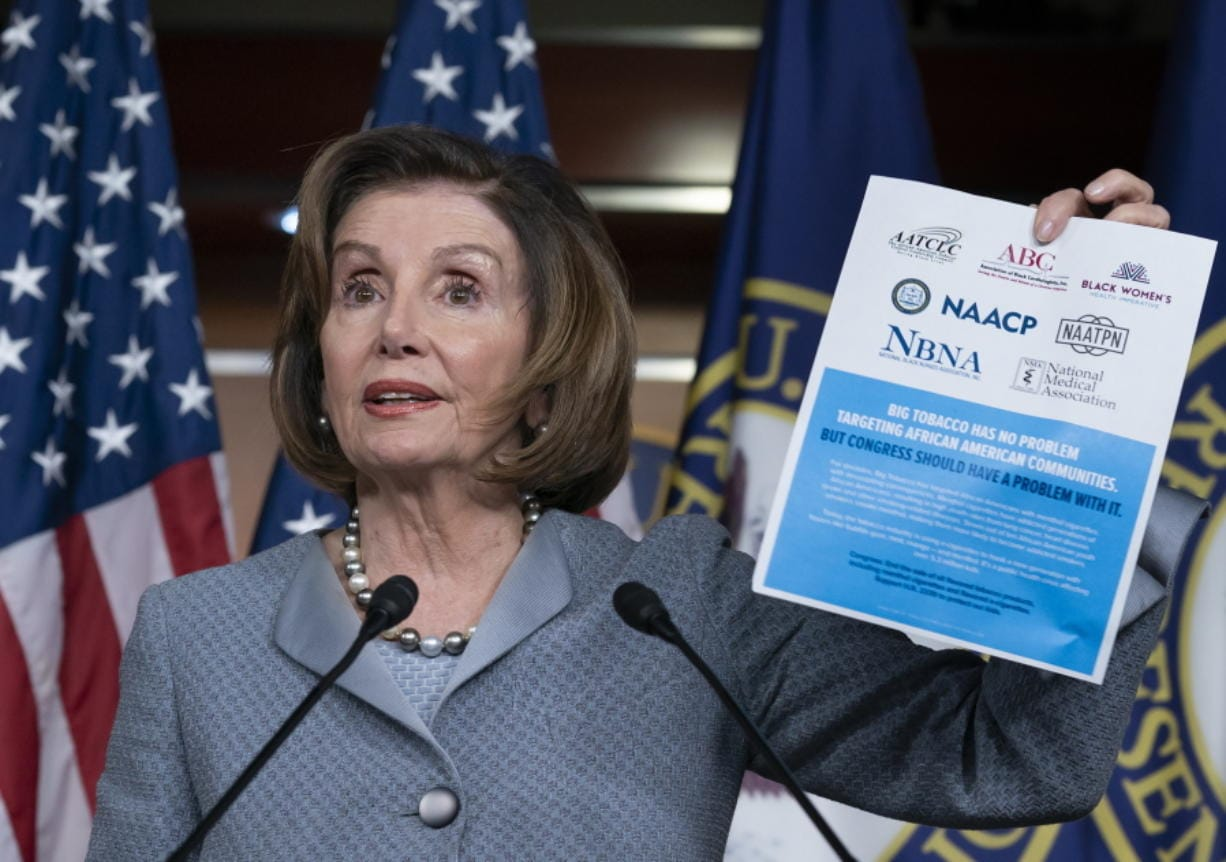 Speaker of the House Nancy Pelosi, D-Calif., displays an advocacy ad that criticizes the tobacco and vaping industry for allegedly targeting young African-Americans, during a news conference on Capitol Hill in Washington, Thursday, Feb. 27, 2020. The House is voting on a measure to reverse the tobacco epidemic among young people. (AP Photo/J.