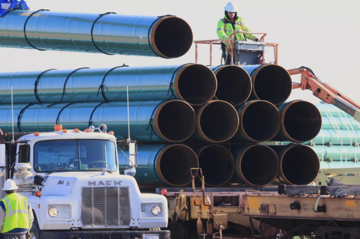 FILE - In this May 9, 2015, file photo, workers unload pipes in Worthing, S.D., for the Dakota Access oil pipeline that stretches from the Bakken oil fields in North Dakota to Illinois. A federal judge on Wednesday, March 25, 2020, ordered the U.S. Army Corps of Engineers to conduct a full environmental review of the Dakota Access pipeline, nearly three years after it began carrying oil.  (AP Photo/Nati Harnik, File)