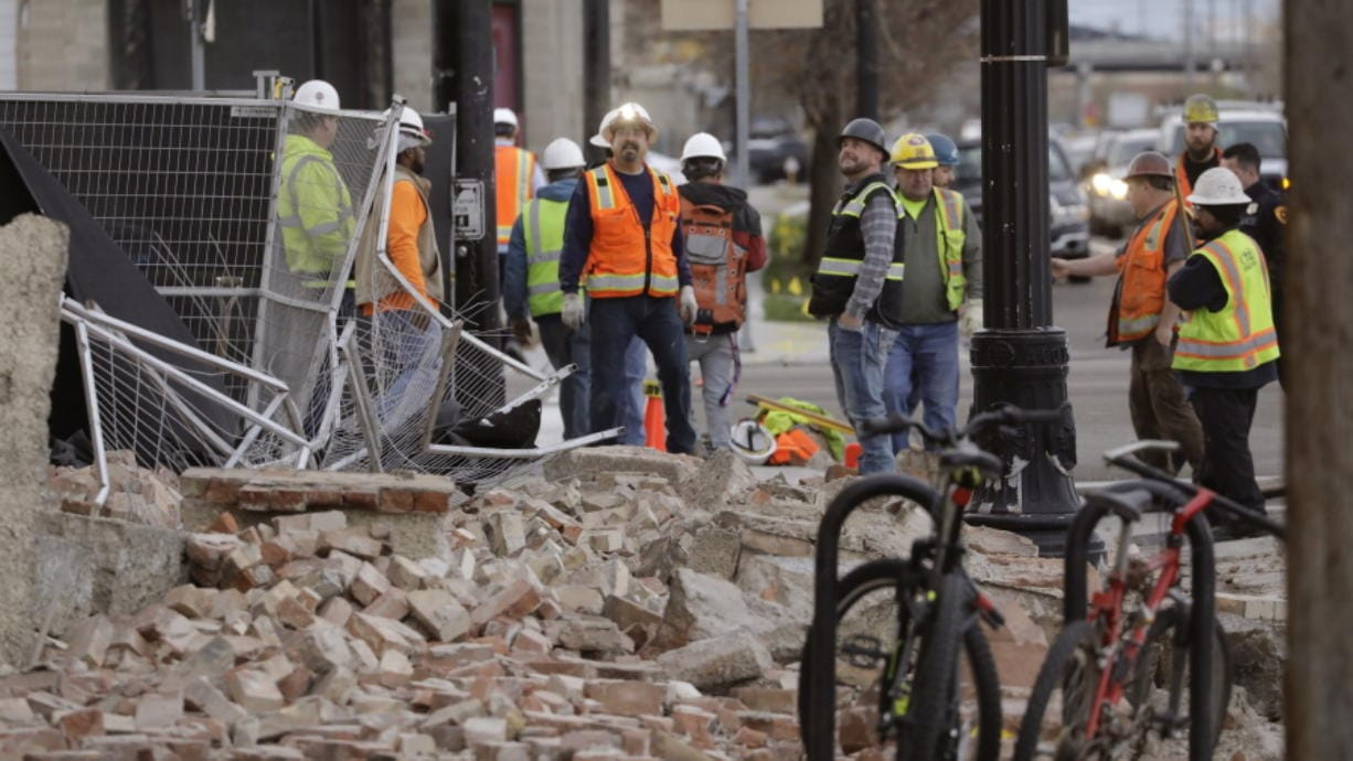 Construction workers looks at the rubble from a building after an earthquake Wednesday, March 18, 2020, in Salt Lake City.  A 5.7-magnitude earthquake has shaken the city and many of its suburbs. The quake sent panicked residents running to the streets, knocked out power to tens of thousands of homes and closed the city's airport and its light rail system.