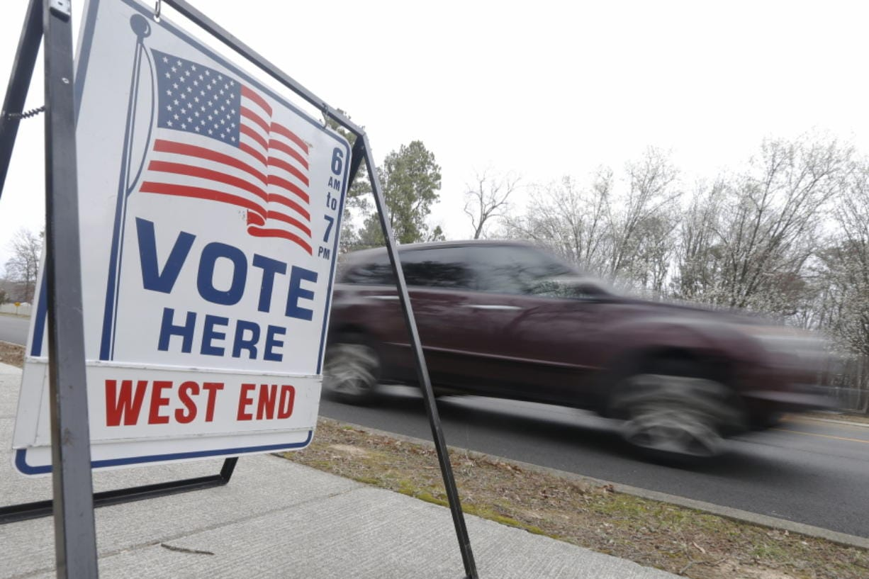A car passes a polling precinct during the Democratic Presidential primary voting Tuesday, March 3, 2020, in Richmond, Va.