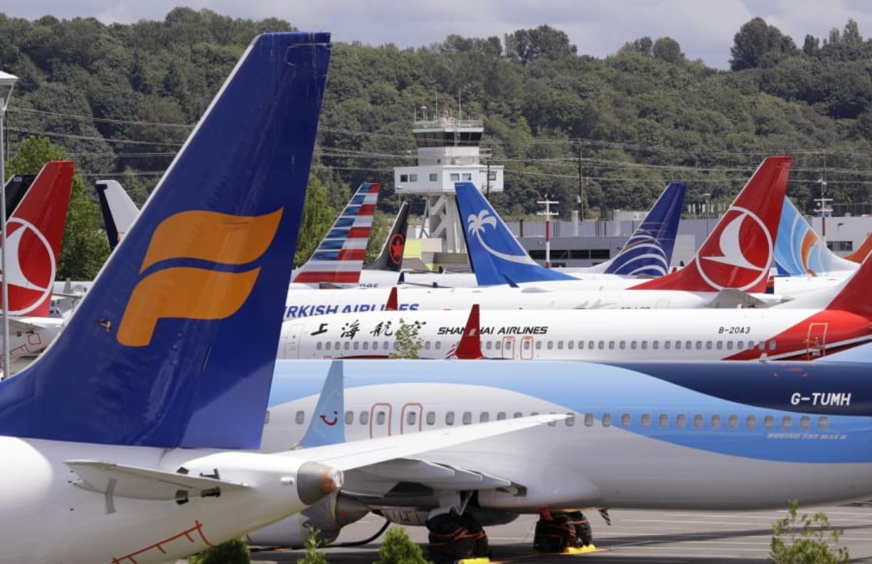 FILE - In this June 27, 2019 file photo, dozens of grounded Boeing 737 MAX airplanes crowd a parking area adjacent to Boeing Field in Seattle. When air safety investigators release an interim report on the crash of an Ethiopian Airlines Boeing 737 Max sometime before Tuesday, March 10, 2020, the one-year anniversary of the crash, they are likely to place the blame on the jet's automated flight control system as well as on the pilots and their training, but it's unclear yet which side will bear the brunt.