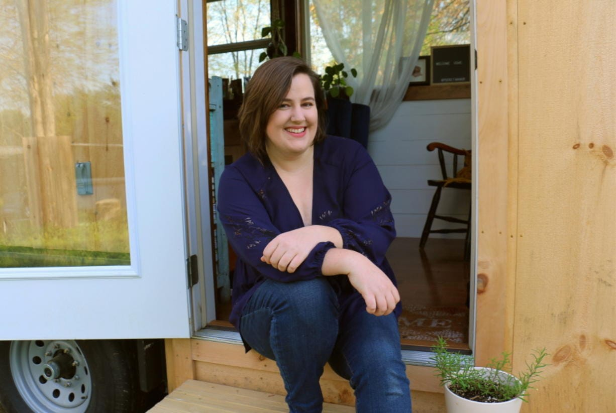 This photo provided by NerdWallet shows Annie Colpitts posing in a doorway of her tiny home, in Ashland, Va. Colpitts designed and helped build the home. (Courtesy of Annie Colpitts/NerdWallet via AP)