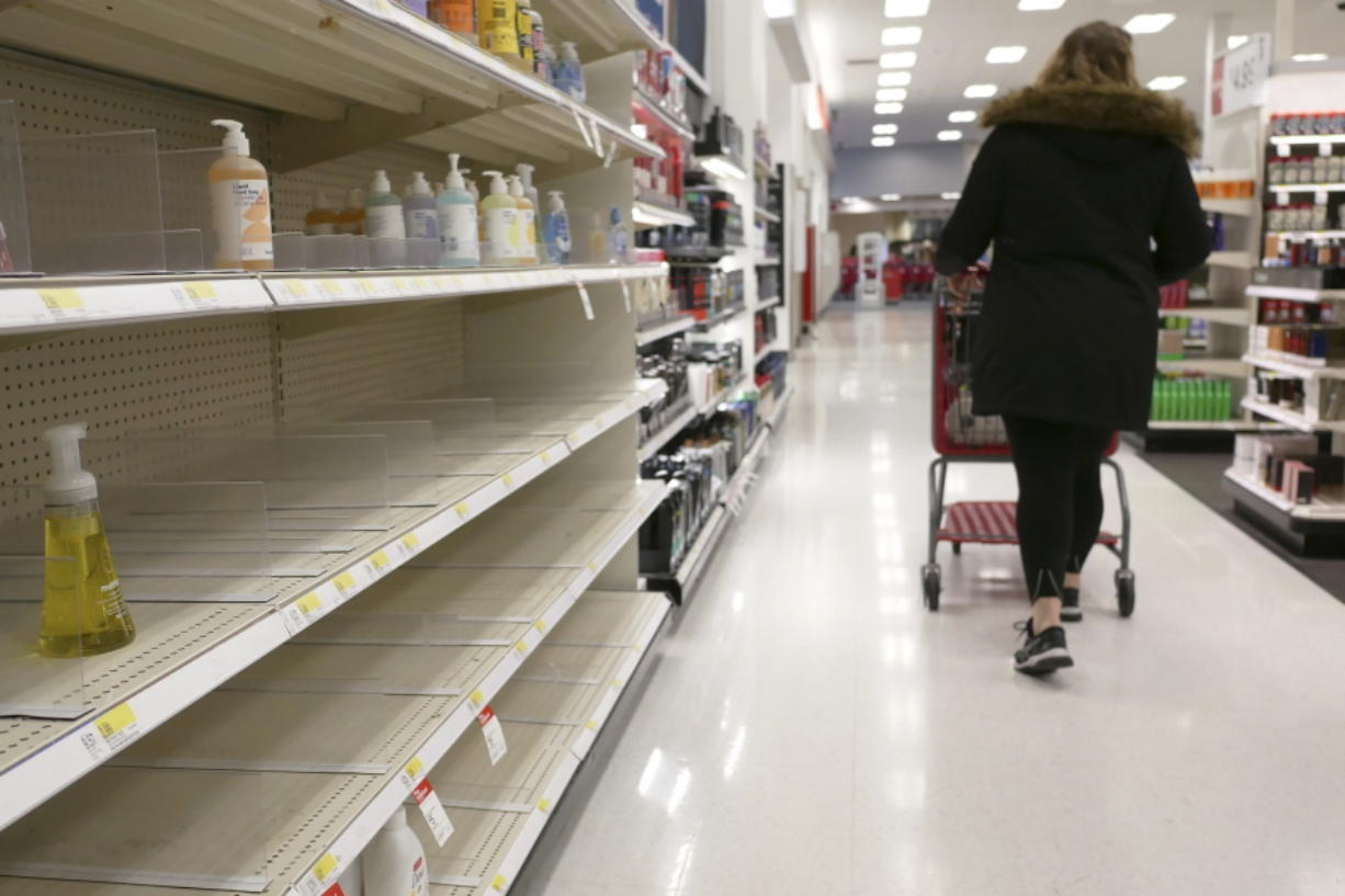 FILE - In this March 3, 2020 file photo, shelves that held hand sanitizer and hand soap are mostly empty at a Target in Jersey City, N.J.    People who may have been exposed to the new coronavirus or who get sick with COVID-19 may be advised to stay home for as long as 14 days to keep from spreading it to others, according to the Centers for Disease Control. That's led many people to wonder if they could manage for two weeks at home without a run to the grocery store.
