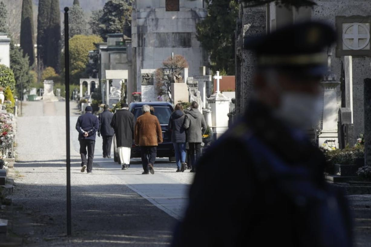 FILE - In this Tuesday, March 17, 2020. filer, relatives walk behind a hearse carrying a coffin inside the Monumentale cemetery, in Bergamo, the heart of the hardest-hit province in Italy's hardest-hit region of Lombardy, Italy.  Italy is seeing a slight stabilizing in its confirmed coronavirus infections two weeks into the world's most extreme nationwide shutdown, but the virus is taking its silent spread south after having ravaged the health care system in the north. The new coronavirus causes mild or moderate symptoms for most people, but for some, especially older adults and people with existing health problems, it can cause more severe illness or death.