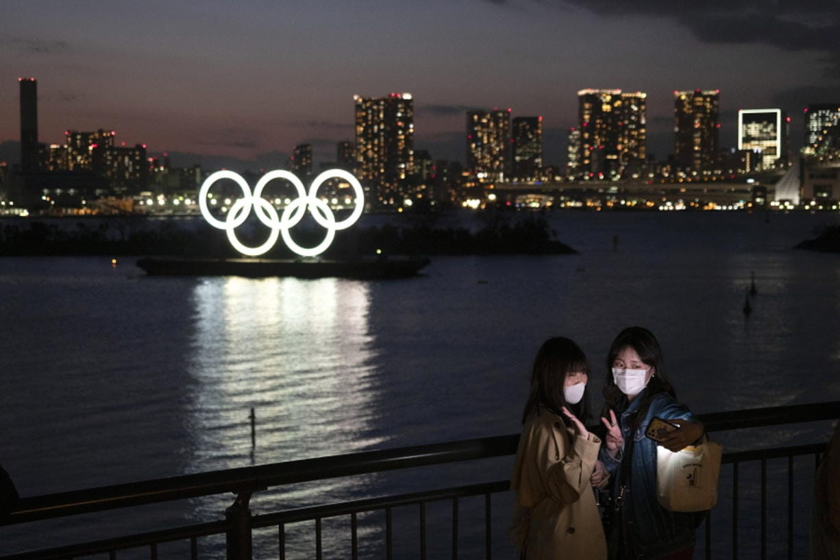 Two women take a selfie with the Olympic rings in the background in the Odaiba section of Tokyo, Thursday, March 12, 2020.  Doping testers around the sporting world are trying to avoid infecting themselves or athletes during the global virus outbreak, and that's not easy when collecting samples means getting very close to sports stars. (AP Photo/Jae C.