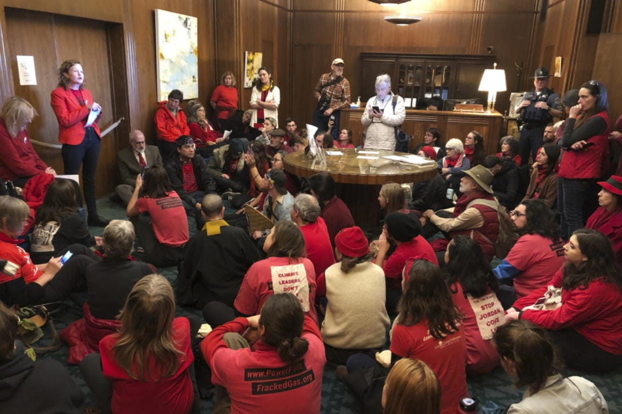 FILE - In this Nov. 21, 2019, file photo, demonstrators against a proposed liquid-natural gas pipeline and export terminal in Oregon sit in in the governor's office in the State Capitol in Salem, Ore., to demand Democratic Gov. Kate Brown stand against the proposal. The Jordan Cove pipeline is undergoing a permitting process and would end at a proposed marine export terminal in Coos Bay, Ore. Members of a federal regulatory agency on Thursday, Feb. 20, 2020, delayed a vote on the project, with one member saying greenhouse gas emissions and endangered species should be considered.