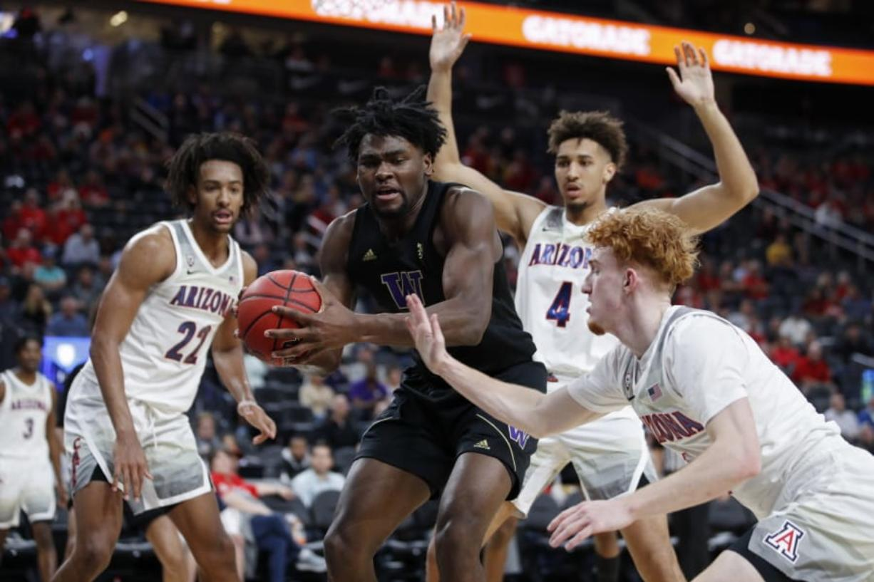 Washington's Isaiah Stewart (33) grabs a rebound over Arizona's Nico Mannion, right, during the first half of an NCAA college basketball game in the first round of the Pac-12 men's tournament Wednesday, March 11, 2020, in Las Vegas.
