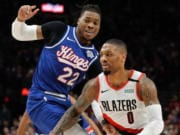 Portland Trail Blazers guard Damian Lillard, right, drives past Sacramento Kings center Richaun Holmes during the first half of an NBA basketball game in Portland, Ore., Saturday, March 7, 2020.