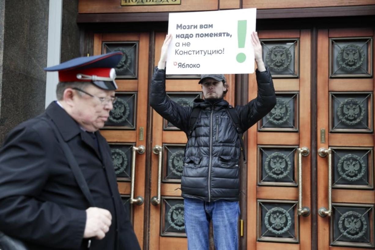 """A member of the liberal Yabloko Party holds a poster reading: """"You need to change the brain, not the constitution!"""" as he stages a one-man picket at the State Duma, the Lower House of the Russian Parliament in Moscow, Russia, Wednesday, March 11, 2020. The Russian parliament has approved a sweeping constitutional reform that will allow President Vladimir Putin to stay in power for another 12 years after his current term ends in 2024. Wednesday's vote was the third and final reading."""