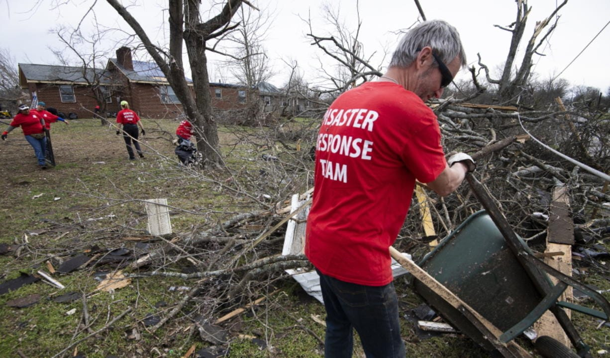 Russ Freeman of Donelson Fellowship church disaster response team works to clean up tornado debris along McGavock Pike on Wednesday in Nashville, Tenn.