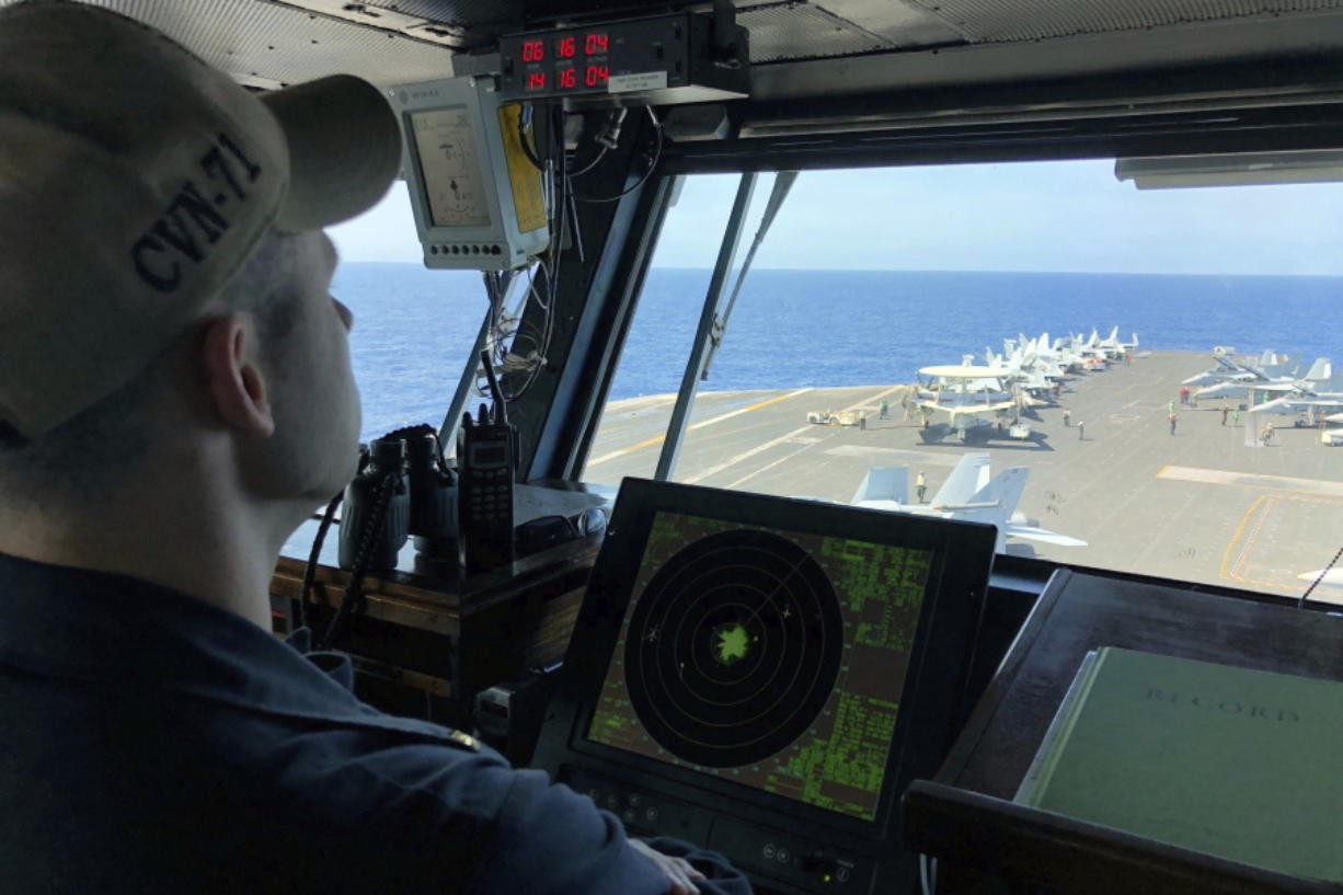 A U.S. Navy crewman monitors the deck of the U.S. aircraft carrier Theodore Roosevelt near the South China Sea in April 2018.