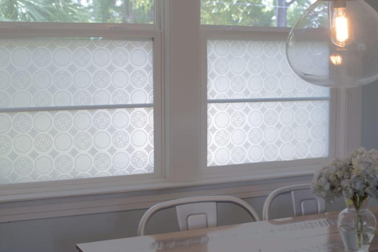 This photo shows StickPretty Gothica window film which shields street views from this family kitchen table while still allowing tree-filled sight lines. (Christy Flannigan/StickPretty)