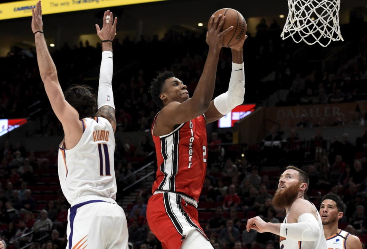 Portland Trail Blazers center Hassan Whiteside, center, drives to the basket on Phoenix Suns guard Ricky Rubio, left, and center Aron Baynes, right, during the first quarter of an NBA basketball game in Portland, Ore., Tuesday, March 10, 2020. (AP Photo/Steve Dykes)