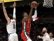 Portland Trail Blazers center Hassan Whiteside, center, drives to the basket on Phoenix Suns guard Ricky Rubio, left, and center Aron Baynes, right, during the first quarter of an NBA basketball game in Portland, Ore., Tuesday, March 10, 2020.