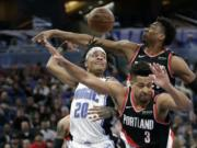 Orlando Magic guard Markelle Fultz (20) passes the ball behind his head as he gets trapped between Portland Trail Blazers center Hassan Whiteside, back right, and guard CJ McCollum (3) during the second half of an NBA basketball game, Monday, March 2, 2020, in Orlando, Fla.