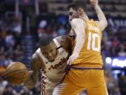 Portland Trail Blazers guard Damian Lillard, left, is fouled as he tries to dribble past Phoenix Suns guard Ty Jerome (10) during the first half of an NBA basketball game Friday, March 6, 2020, in Phoenix. (AP Photo/Ross D.