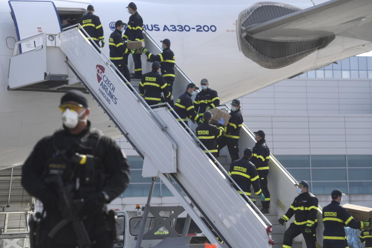 A police officer stands guard as firefighters unload an airplane Friday at the Vaclav Havel Airport in Prague. The plane brought medical aid and protective equipment from China.