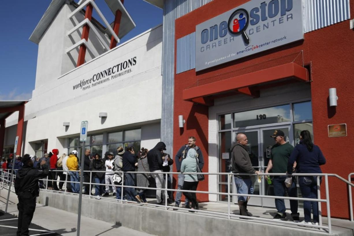FILE - In this March 17, 2020 file photo, people wait in line for help with unemployment benefits at the One-Stop Career Center in Las Vegas.   A record-high number of people applied for unemployment benefits last week as layoffs engulfed the United States in the face of a near-total economic shutdown caused by the coronavirus. The surge in weekly applications for benefits far exceeded the previous record set in 1982.