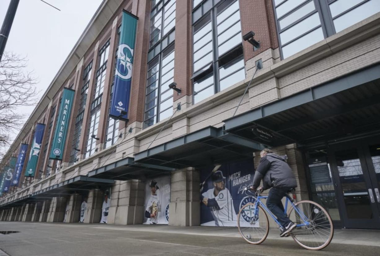 A bicyclist rides past T-Mobile Park, Wednesday, March 11, 2020, in Seattle, where baseball's Seattle Mariners plays home games. In efforts to slow the spread of the COVID-19 coronavirus, Washington State Gov. Jay Inslee announced a ban on large public gatherings in three counties in the metro Seattle area. That decision impacts the Seattle Mariners, Seattle Sounders, and the XFL's Seattle Dragons home games.