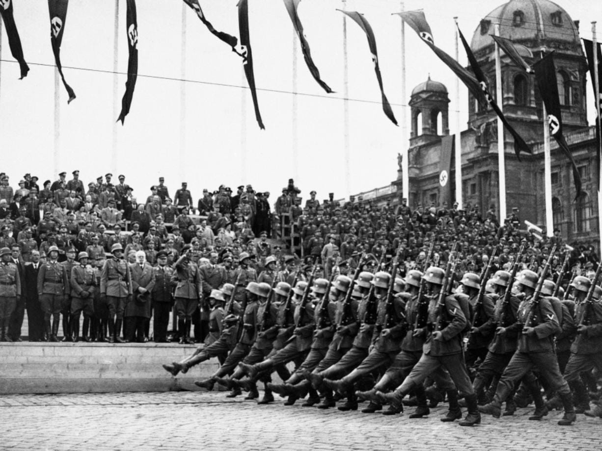 FILE - In this March 24, 1938, file photo, German standard bearers parade past Maj. Gen. Fedor von Bock, commander of all armed forces in the Austrian territory, center, on grandstand on the Kingstrasse in front of the Memorial of Honor, as the troops reach Vienna. Beside him wearing overcoat is Dr. Seysz Incuart. World War II references are now heard daily, not because another momentous 75th anniversary, Victory in Europe Day approaches in May but because of the coronavirus. (AP Photo, File)