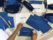 """In this Sunday, March 22, 2020, photo, provided by Christina Hunter, Briana Danyele sews cloth face masks that say """"We Got This!"""" in her mother's living room in Greer, S.C., which will be sent to health care workers. Legions of everyday Americans are sewing masks for desperate hospitals, nursing homes and homeless shelters amid the expanding coronavirus pandemic."""