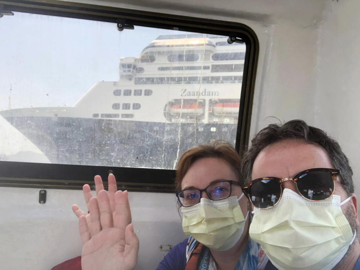 In this March 28, 2020 photo provided by Juan Huergo, Laura Gabaroni and her husband Juan Huergo take a selfie on board a tender after they were evacuated from the Zaandam, a Holland American cruise ship, near the Panama Canal. The Orlando- area couple was transferred to the Rotterdam, together with others who were deemed healthy. Four people have died on board the Zaandam and many others have are suffering from flu-like symptoms.