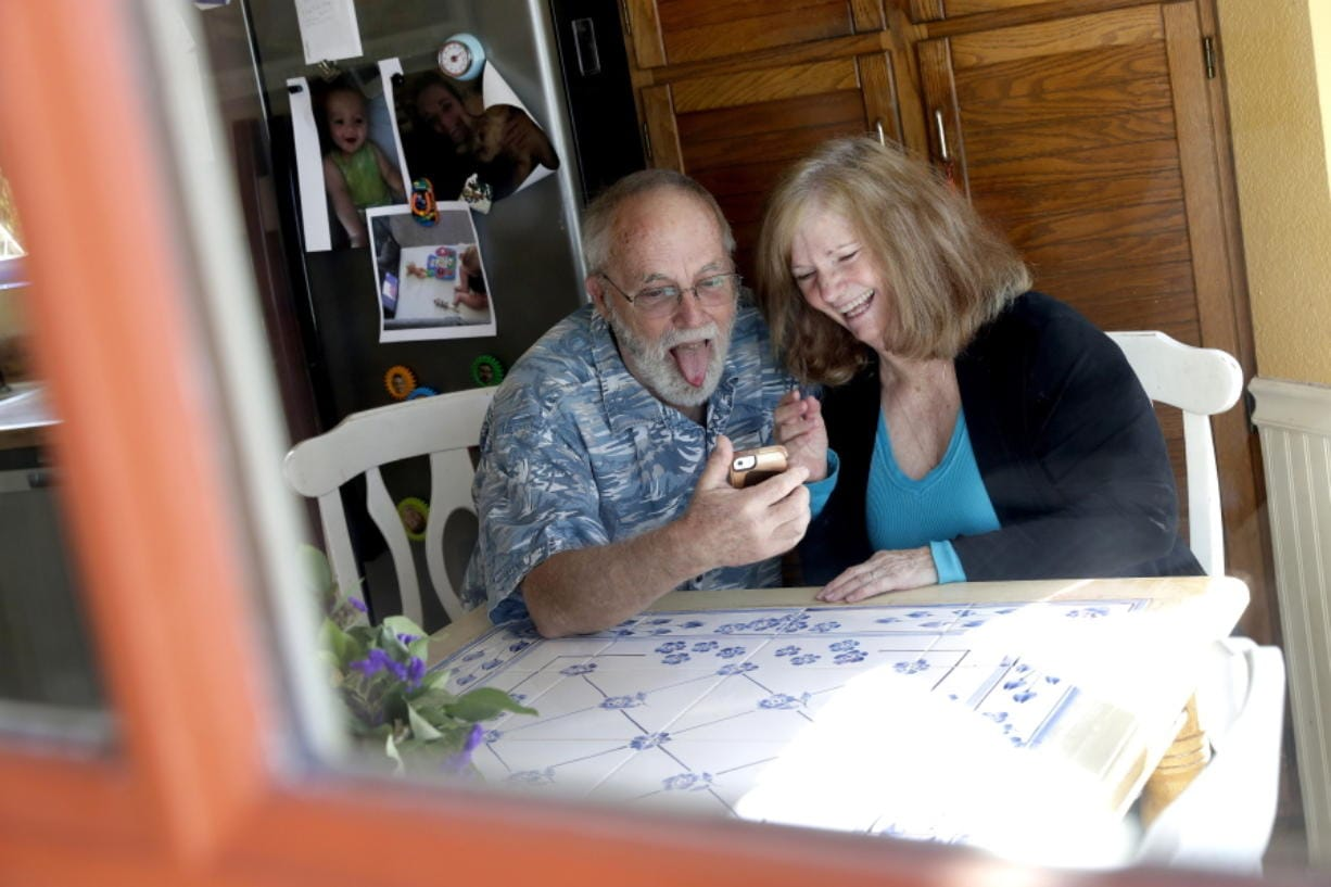 Seen through their kitchen window, Allan and Debbie Cameron contact their grandchildren via the internet Wednesday, March 25, 2020, in Chandler, Ariz. Debbie, 68, has asthma which makes her one of the people most at risk from the new coronavirus. The Cameron's now she see their children and grandchildren from the other side of a window or a phone.