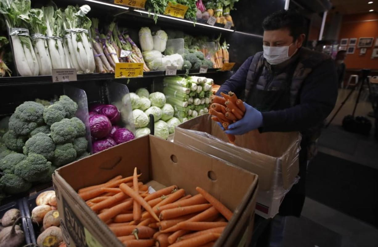 A worker, wearing a protective mask against the coronavirus, stocks produce before the opening of Gus's Community Market, on Friday in San Francisco.