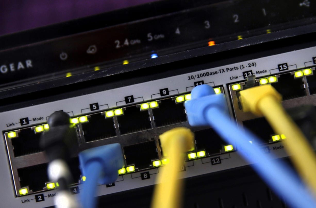 FILE - In this June 19, 2018, file photo, a router and internet switch are displayed in East Derry, N.H.   With so much of the U.S. workforce,  and their families, now cooped up at home to combat the spread of  coronavirus, it's not a huge surprise that home internet is showing the strain. Will there be a bandwidth problem with all the devices going at once?
