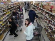 Shoppers stock up on canned items at WinCo Foods Friday, March 13, 2020 in Idaho Falls, Idaho. Idaho Gov. Brad Little declared a state of emergency Friday because of the new coronavirus.