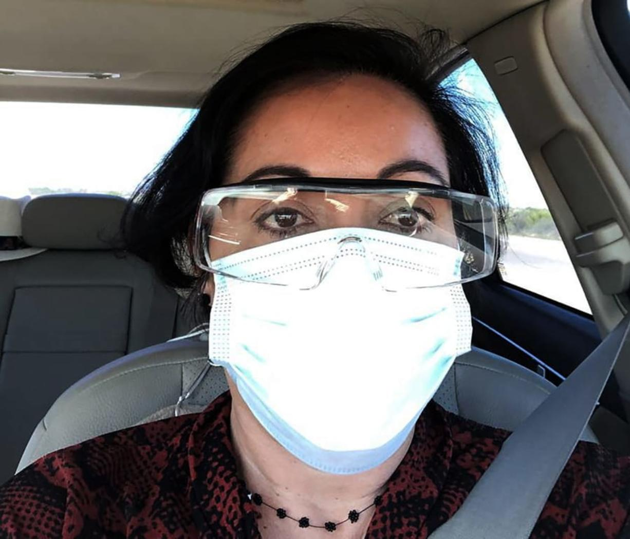 This March 23, 2020 photo provided by Margarita Silva shows her wearing her husband's land surveyor goggles, a mask she borrowed from a friend and medical gloves she got from a hardware store outside the La Palma Detention Center in Eloy, Ariz. Attorneys and judges in U.S. immigration courts are trying to protect themselves from the coronavirus with borrowed masks and hand sanitizer. The Trump administration has delayed hearings for immigrants who aren't in detention but is moving forward for those who are.