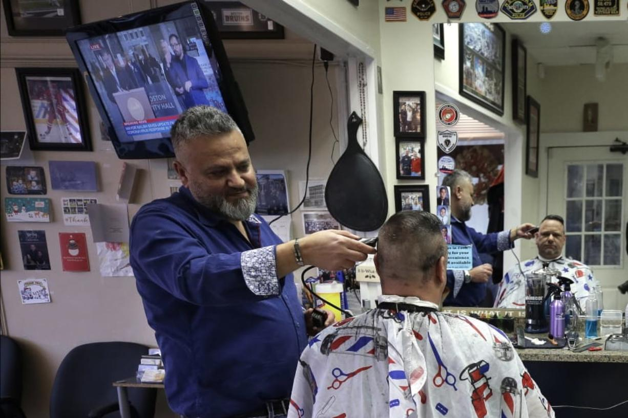 Barber Sami Matta, left, gives a haircut to Steve Perosino, of Dedham, Mass., right, at Chris & Sam's Barbershop, in Norwood, Mass., Monday, March 23, 2020. The Barbershop is to close by noon Tuesday, March 24, in keeping with Mass. Gov. Charlie Baker's order that all non-essential businesses close at noon Tuesday and remain closed through Tuesday, April 7, out of concern about the spread of the coronavirus. For most people, the new coronavirus causes only mild or moderate symptoms, such as fever and cough. For some, especially older adults and people with existing health problems, it can cause more severe illness, including pneumonia. The vast majority of people recover from the new virus. (AP Photo/Steven Senne)