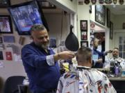 Barber Sami Matta, left, gives a haircut to Steve Perosino, of Dedham, Mass., right, at Chris & Sam's Barbershop, in Norwood, Mass., Monday, March 23, 2020. The Barbershop is to close by noon Tuesday, March 24, in keeping with Mass. Gov. Charlie Baker's order that all non-essential businesses close at noon Tuesday and remain closed through Tuesday, April 7, out of concern about the spread of the coronavirus. For most people, the new coronavirus causes only mild or moderate symptoms, such as fever and cough. For some, especially older adults and people with existing health problems, it can cause more severe illness, including pneumonia. The vast majority of people recover from the new virus.
