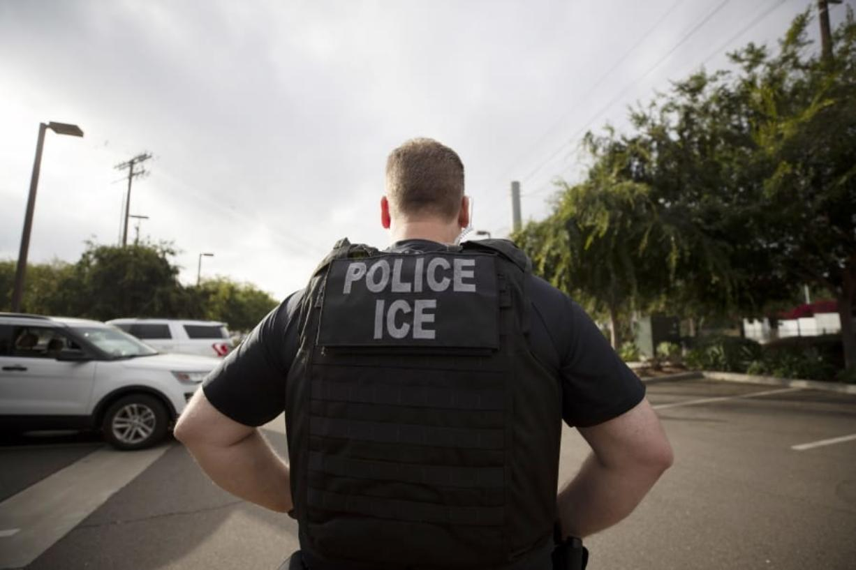 FILE - In this July 8, 2019, file photo, a U.S. Immigration and Customs Enforcement (ICE) officer looks on during an operation in Escondido, Calif.  Pressure is mounting on the Trump administration to release people from immigration detention facilities where at least one detainee has already tested positive for COVID-19.
