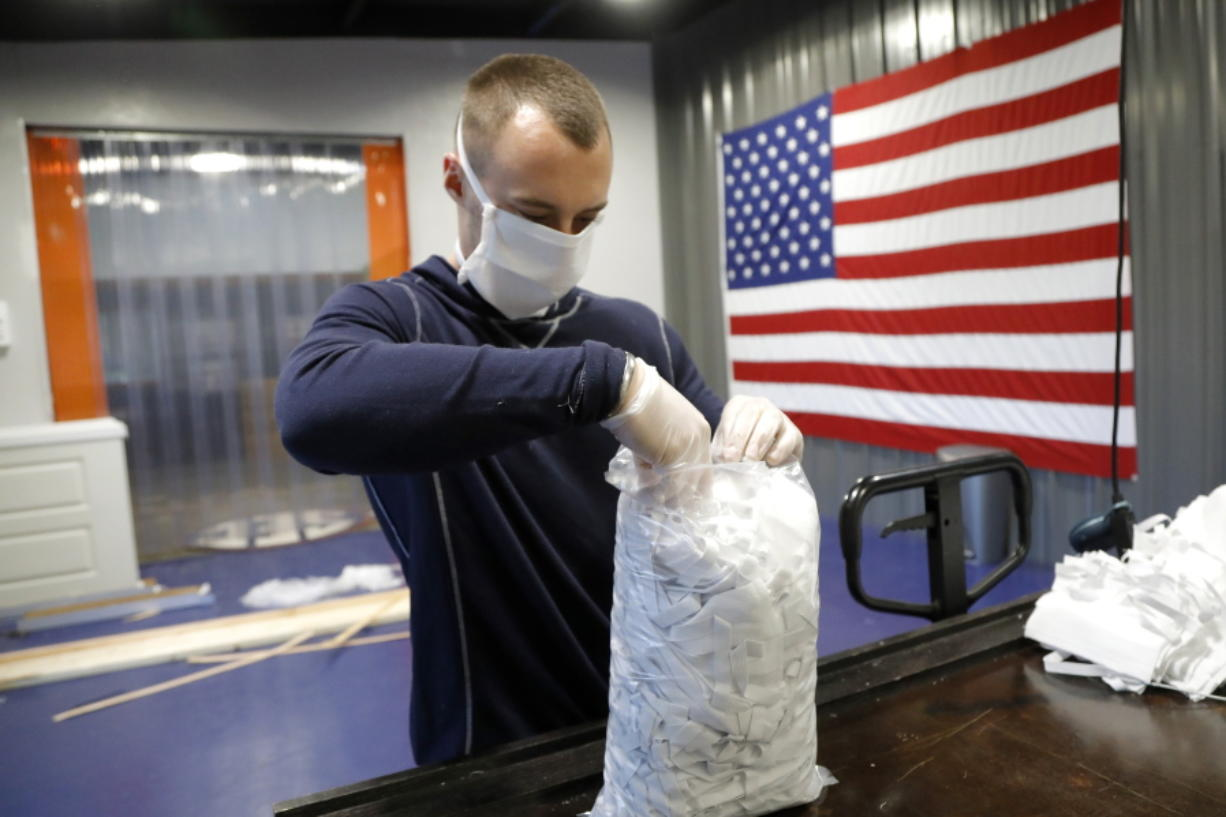 In this Thursday, March 26, 2020 photo, A.J. Davidson, who works in the business development department at Blue Delta Jeans, packages face guards made at the jeans manufacturing site in Shannon, Miss. The company has shifted its operation from making custom jeans to help with the demand of face masks to combat the coronavirus outbreak. The new coronavirus causes mild or moderate symptoms for most people, but for some, especially older adults and people with existing health problems, it can cause more severe illness or death.