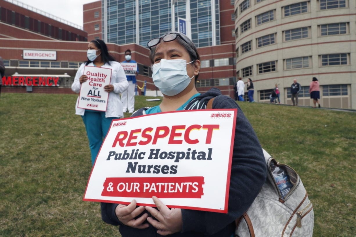 Nurses stand on a grassy hill outside the emergency entrance to Jacobi Medical Center in the Bronx borough of New York, Saturday, March 28, 2020, as they demonstrate with members of the New York Nursing Association in support of obtaining an adequate supply of personal protective equipment for those treating coronavirus patients. A member of the New York nursing community died earlier in the week at another New York hospital. The city leads the nation in the number of coronavirus cases. Nurses say they are having to reuse their protective equipment endangering patients and themselves.