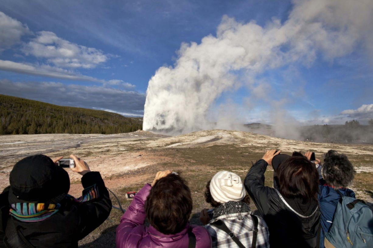 FILE - In this May 21, 2011 file photo, tourists photograph Old Faithful erupting on schedule late in the afternoon in Yellowstone National Park, Wyo.