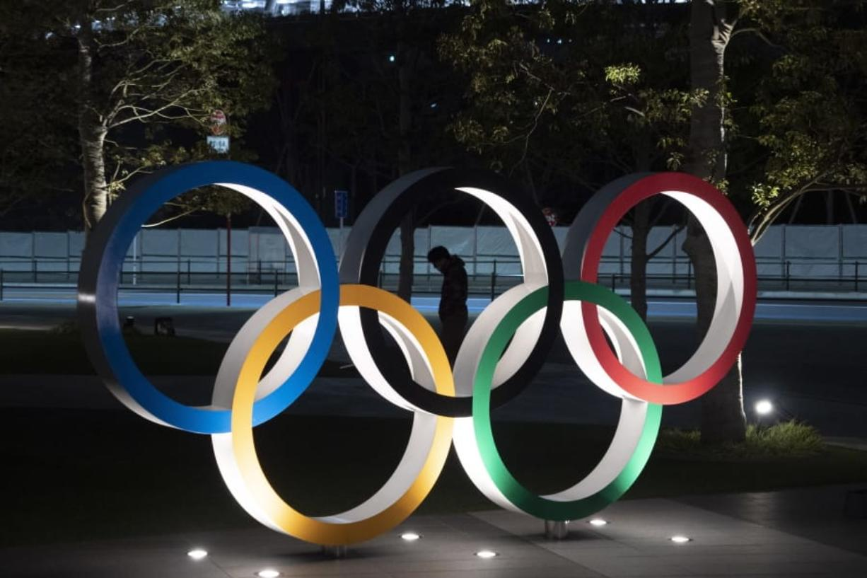 """A man is seen through the Olympic rings in front of the New National Stadium in Tokyo, Tuesday, March 24, 2020. IOC President Thomas Bach has agreed """"100%"""" to a proposal of postponing the Tokyo Olympics for about one year until 2021 because of the coronavirus outbreak, Japanese Prime Minister Shinzo Abe said Tuesday. (AP Photo/Jae C."""