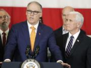 Vice President Mike Pence, right, looks on as Gov. Jay Inslee speaks during a news conference, Thursday, March 5, 2020, at Camp Murray in Washington state. Pence was in Washington to discuss the state's efforts to fight the spread of the COVID-19 coronavirus. Inslee's office announced Monday the governor won't hold any more public bill signings due to concerns about COVID-19. (AP Photo/Ted S.